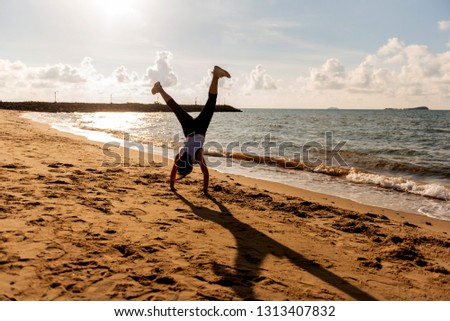 Silhouette woman somersault and exercise on the beach sunset. Sport and healthy lifestyle. Fresh start of day and recreation. #1313407832