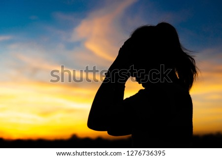 Silhouette woman standing sad in the sunset. #1276736395