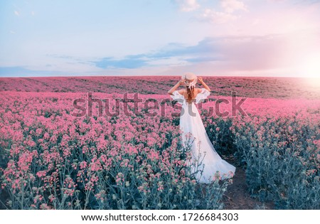 silhouette woman. white long vintage dress. Princess medieval lady in historical clothes. Straw hat boater flowers. Aroma spring nature pink flowering field, blue sky sunset sun light. back rear view