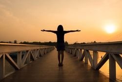 Silhouette woman with hands rise up on beautiful view (similar christian cross) at wooden bridge with orange sky,believe in god concept