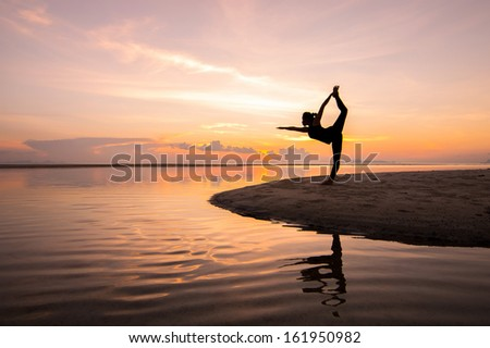 Silhouette woman with yoga posture on the beach at sunset with reflection