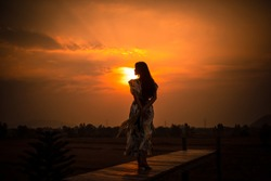 silhouette women walking on the wood bridge and over light the sunset background