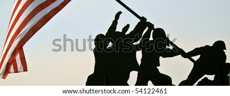 Silhouette wood cutout of American servicemen raising the American Flag. A real United States flag blows in the wind. Warm morning sunlight background.