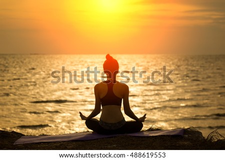 Silhouette yoga, Asia young woman practicing yoga on the beach . #488619553