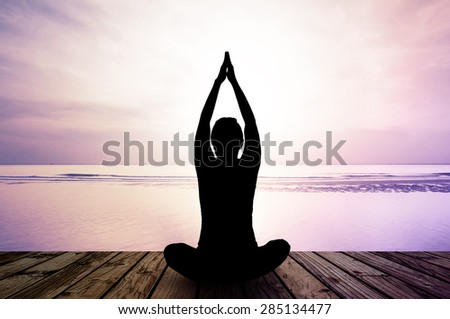 silhouette yoga practicing at sunset meditation