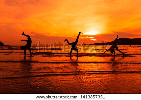 Silhouette young boys doing somersault gymnastic position on the sand beach and sunset seascape background.Happy and funny time together concept. #1413857351