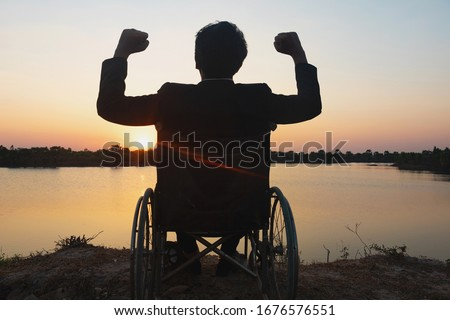 Silhouette young disabled man seeing river background.He is raise a hand to and sitting on wheelchair.despair,lonely,hope.Photo concept depression and Patient.