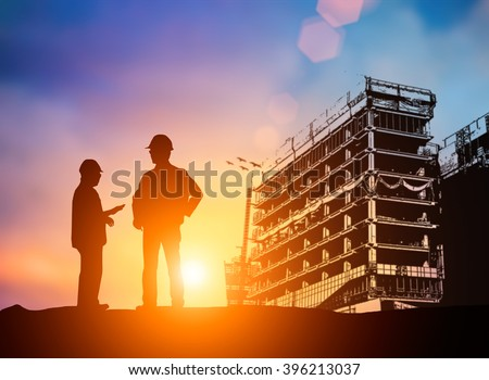silhouette young engineer working construction standards in line with global construction environment and the environment around the work site. Blurred construction worker on construction site.