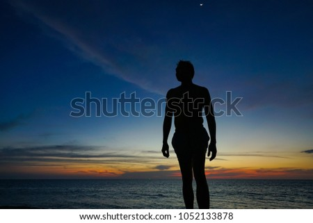 Silhouette young man on the ocean beach and sunset time #1052133878