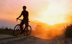 Silhouette young of cyclist on a gravel bike riding on a dust trail at sunset.