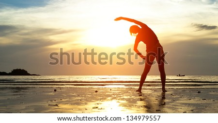Silhouette young woman, exercise on the beach at sunset. Foto stock ©