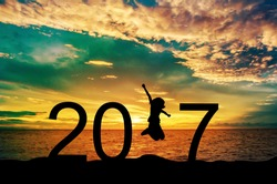 Silhouette young woman jumping on the sea and 2017 years while celebrating new year