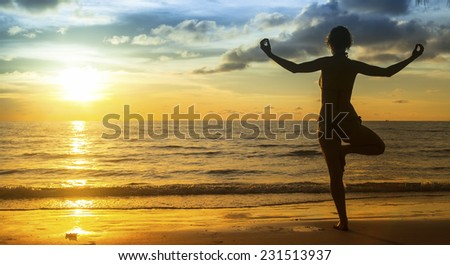 Silhouette young woman practicing yoga on the beach at amazing sunset