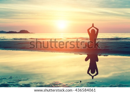 Silhouette young woman practicing yoga on the beach at amazing sunset. #436584061