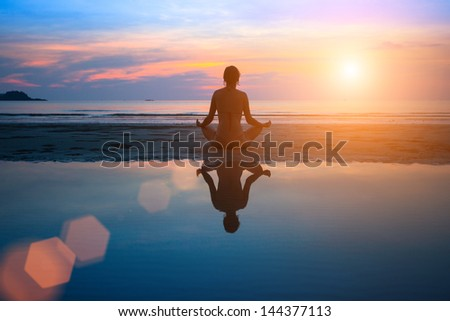 Silhouette young woman practicing yoga on the beach at sunset