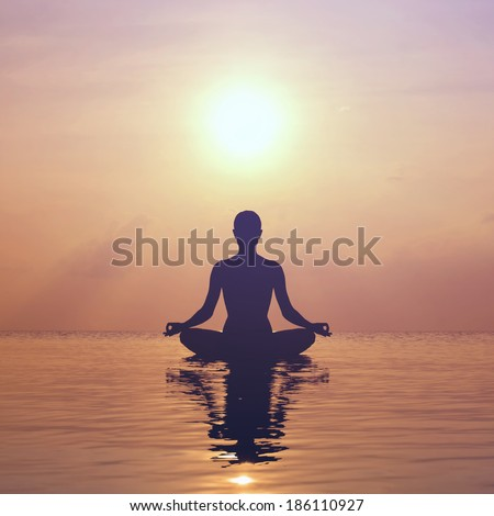 Silhouette young woman practicing yoga on the beach at sunset #186110927