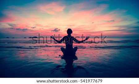 Silhouette young woman practicing yoga on the beach at sunset. #541977679