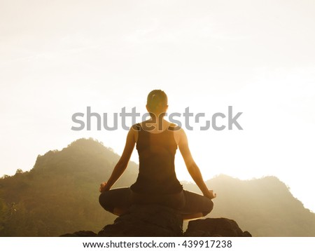 Silhouette young woman practicing yoga on the beach at sunset,Lens Flare. #439917238