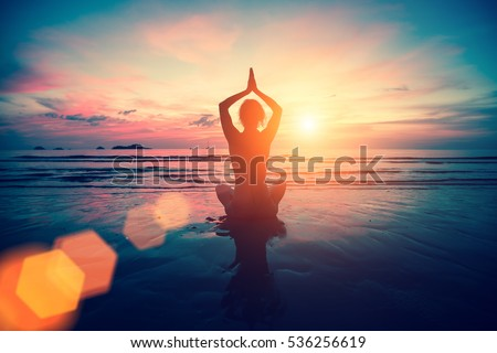 Silhouette young woman practicing yoga on the beach at sunset. Meditation. #536256619