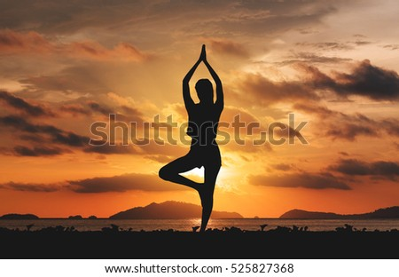 Silhouette young woman practicing yoga on the beach in sunset. #525827368
