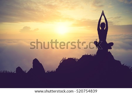 Silhouette young woman practicing yoga on the muontain at sunset.Vintage color #520754839