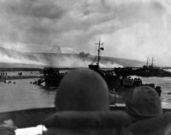 Silhouetted by helmets, view shows two landing craft at Omaha beach on D-Day. Each large ship landed 200 soldiers. June 6, 1944, World War 2.