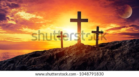 Silhouetted christian cross silhouette on the mountain at sunset #1048791830