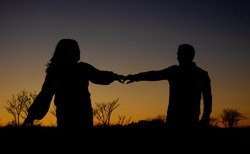 Silhouetted couple dancing at sunset