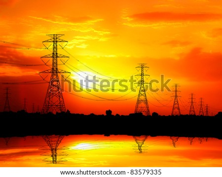 silhouetted electric pylon with power line at sunset