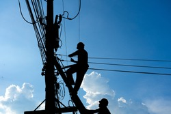 Silhouetted electricians working at electric pole in blue sky background.