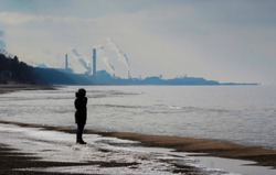 Silhouetted figure stands on south shore of Lake Michigan with steel mills in background