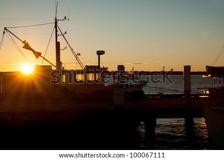 "Silhouetted fishing boat at wharf with the international ""boat fishing"" signal just above the sun burst - stock photo"
