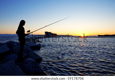 Silhouetted girl fishing from a scenic breakwater.