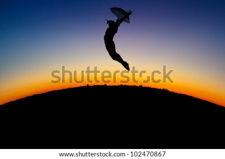 silhouetted girl jumps with umbrella in sunset
