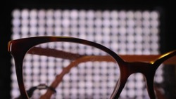 Silhouetted Glasses against bokeh grid background