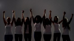 Silhouetted group of diverse women holding, raising their arms together while standing over grey background. Diversity, unity concept. Selective focus. Front view. Web Banner