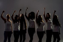 Silhouetted group of diverse women raised their arms, fists while standing over grey background. Diversity, womens rights concept. Selective focus. Horizontal shot