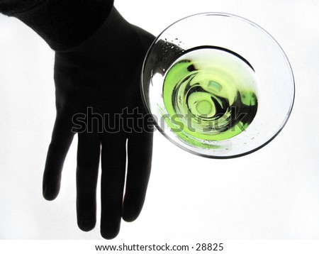 silhouetted hand holding a glass of martini, overhead shot. - stock photo