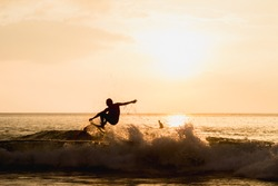 silhouetted image of a surfer showing good performance of arial maneuver