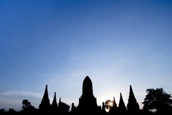 Silhouetted image of chaiwatthanaram temple in the evening when the sun is about to set.