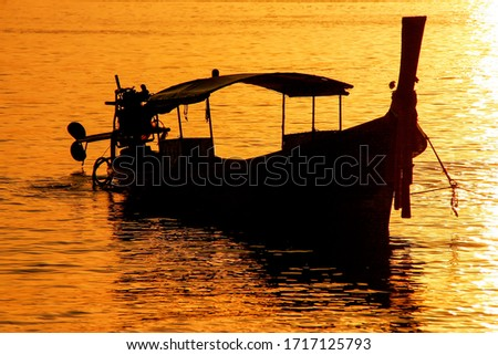 Silhouetted longtail boat at sunrise on Ao Ton Sai, Phi Phi Don Island, Krabi Province, Thailand. Koh Phi Phi Don is part of a marine national park.