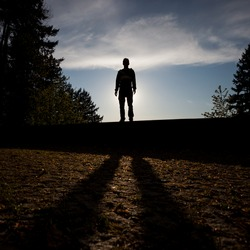 silhouetted man standing on wall in sunset