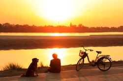 Silhouetted man with a dog watching sunset at Mekong river waterfront, Vientiane, Laos, Southeast Asia
