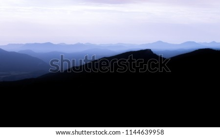 Silhouetted mountain range in blue tones with hazy skies due to forest fires