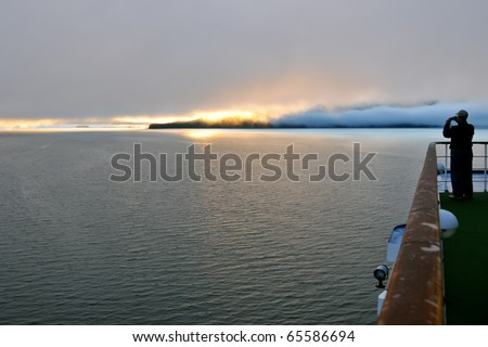 silhouetted passenger photographs dramatic alaskan sunrise from cruise ship deck as travel background