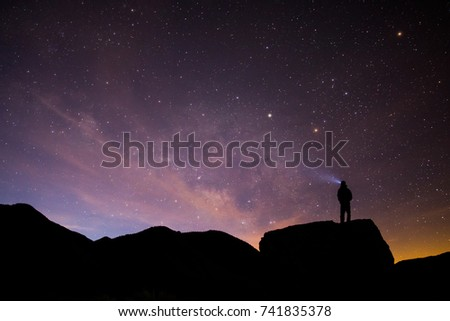 Silhouetted person stands atop boulder with light beam looking up at the milky way and sunrise.