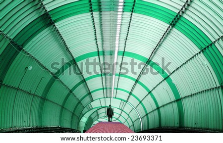 Silhouetted Person walking on red pathway at green metro tube tunnel - stock photo