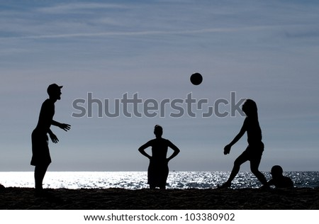 silhouetted teens playing beach volleyball on beach