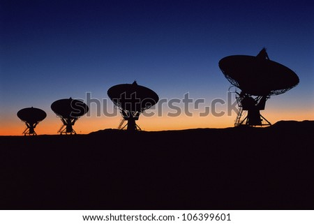 Silhouetted VLA Very Large Array radio telescope dishes