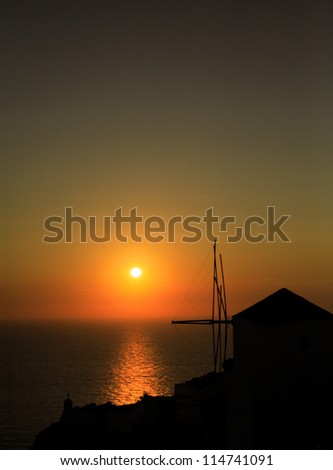 Silhouetted windmill at sunset Santorini Greece